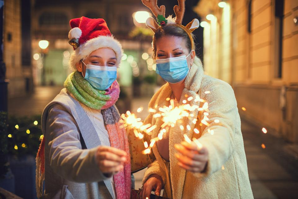 Family having fun while celebrating Christmas during COVID-19 pandemic. They wears a protective mask to protect from coronavirus COVID-19.
