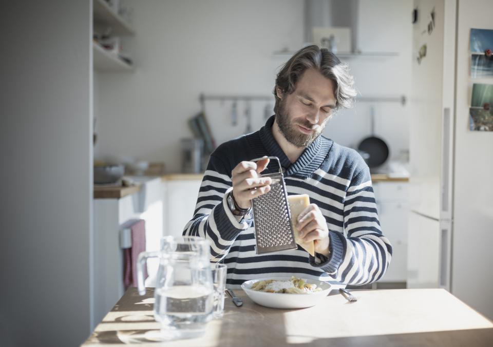 Portrait of bearded man eating at home