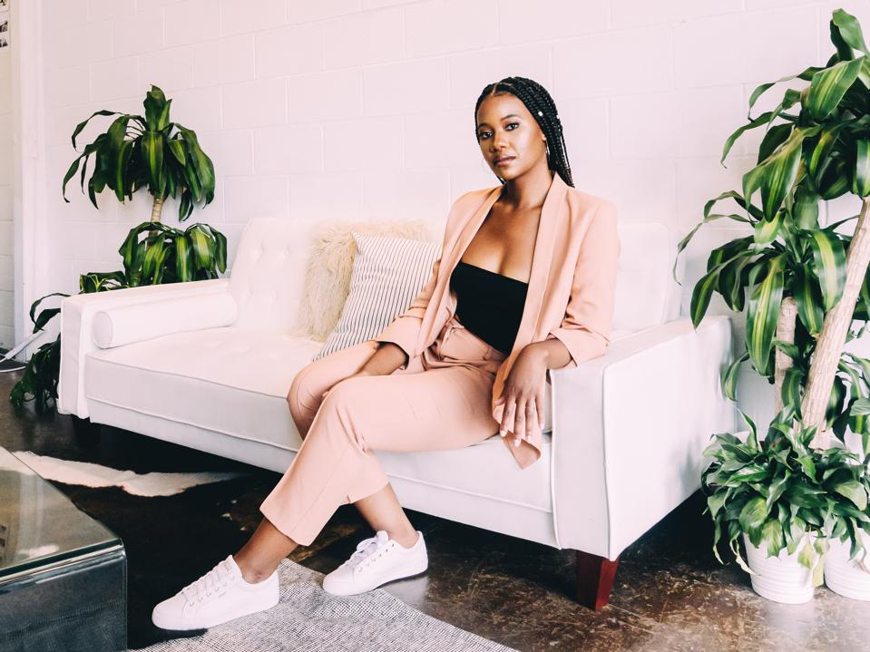 A black woman dressed in a peach blazer and matching pants sits on a white couch.