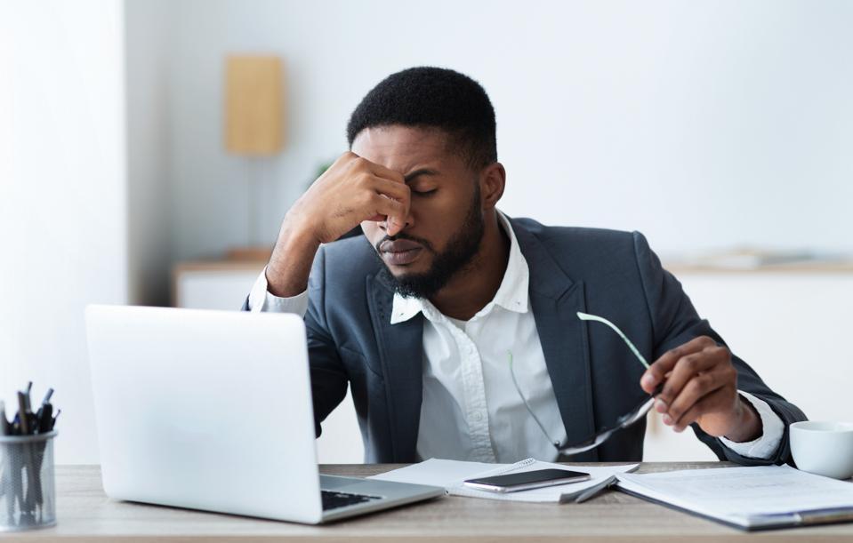 Stressed businessman working at desk.