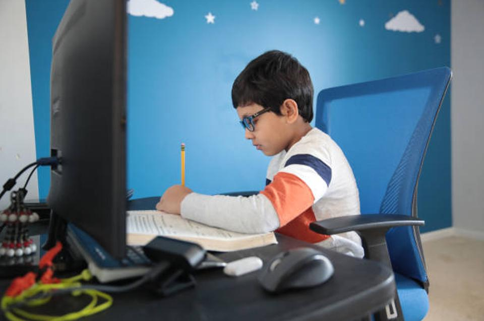 Young male student completes homework while engaging in online learning.