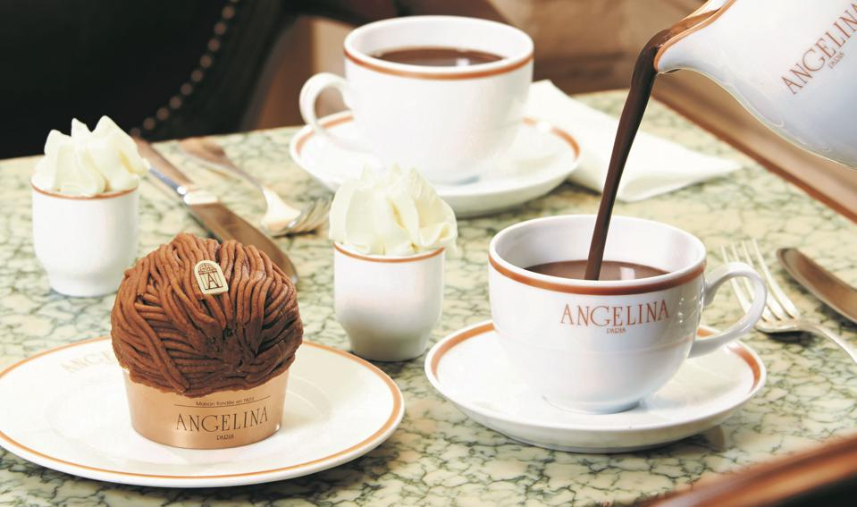 A pastry with strands of chestnut vermicelli and a china pitcher pouring hot chocolate.