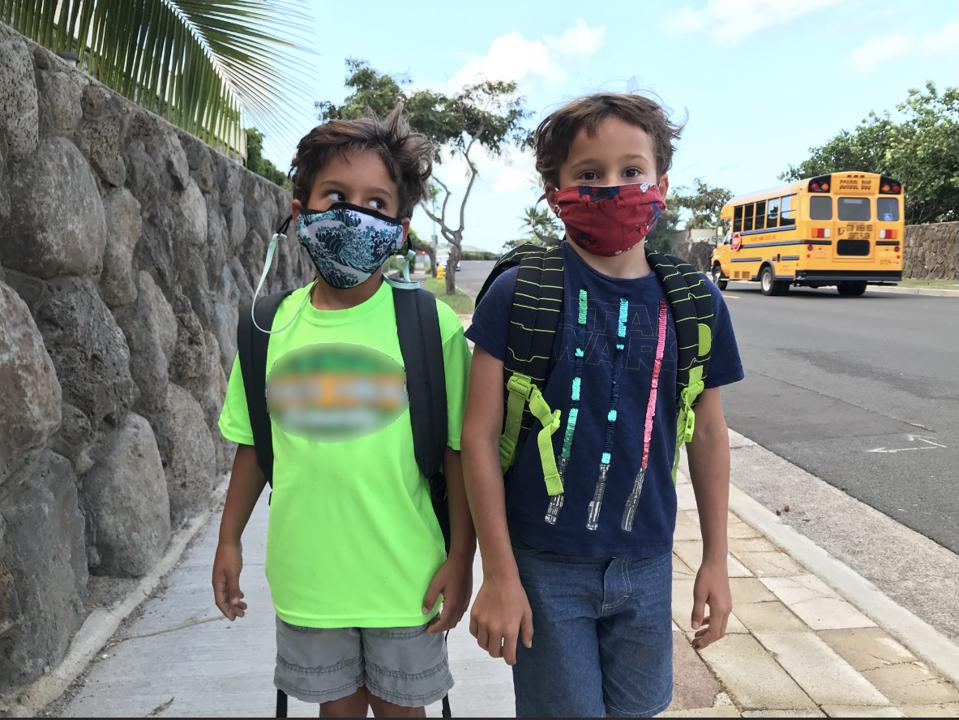 Two 5-year-old boys wearing face masks walk down a street with a school bus in the background.