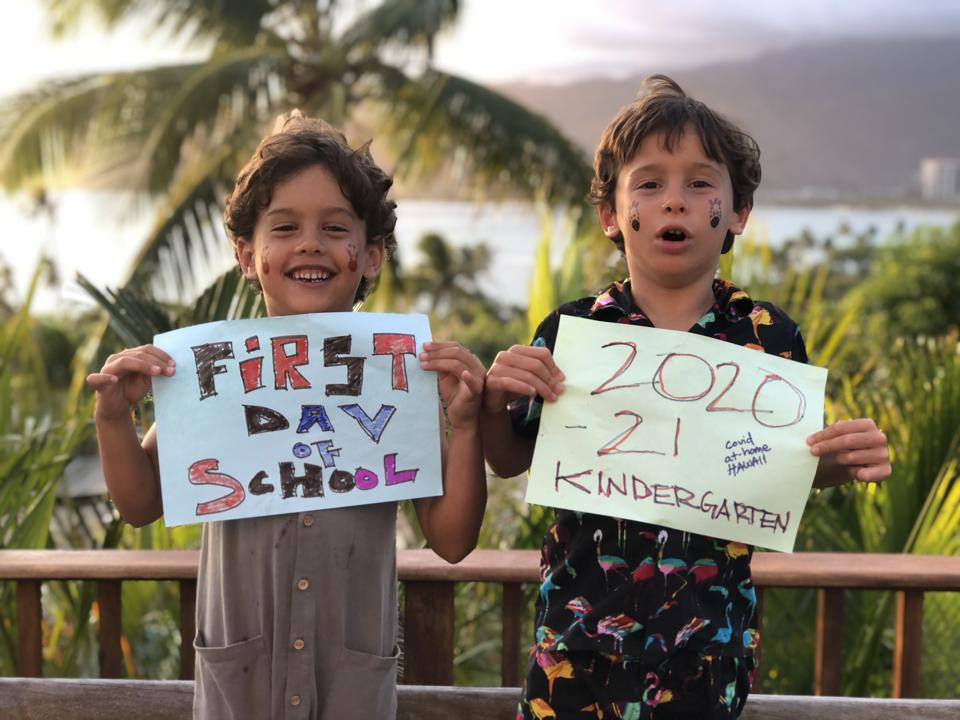Two boys hold up signs that read ″First Day of School, 2020-21 Kindergarten″
