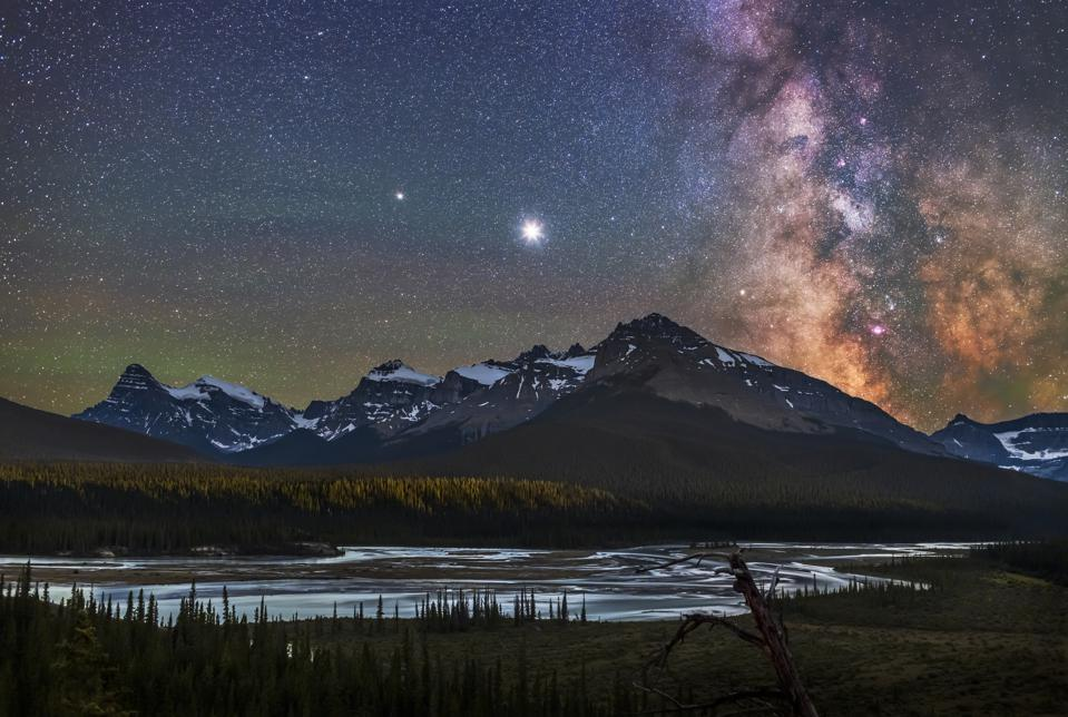 Jupiter (brightest), Saturn (to the left), and the Milky Way over the Saskatchewan River and the area of Howse Pass, on July 26, 2020. Mount Cephren is at left; the scene is framed to include Cephren. The nebulas and star clouds of the galactic centre are