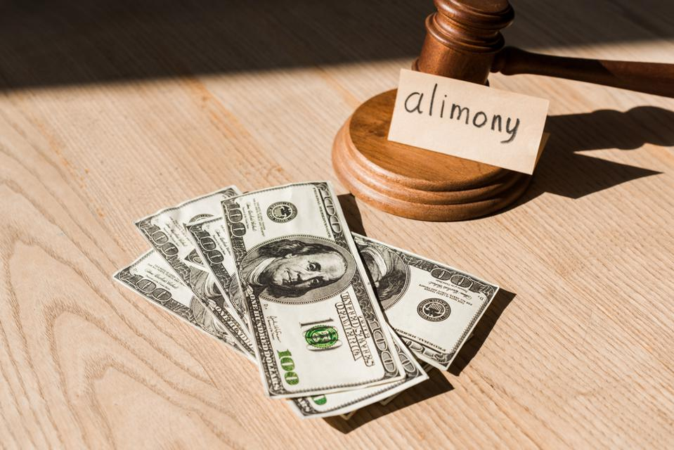 Money, a judge's gavel and a sign saying alimony.
