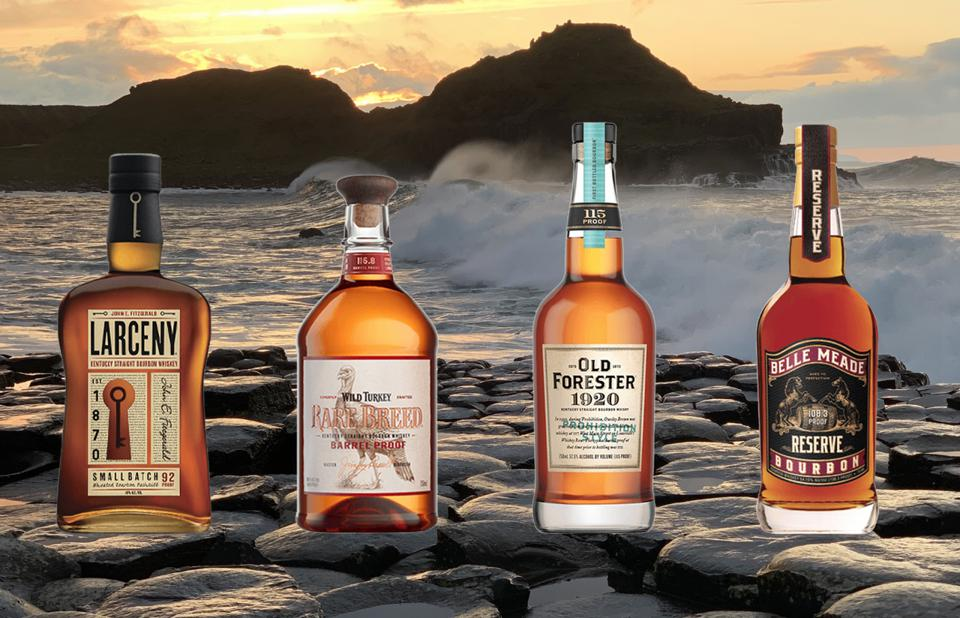 Four bottles of bourbon sit on the shore at sunset.