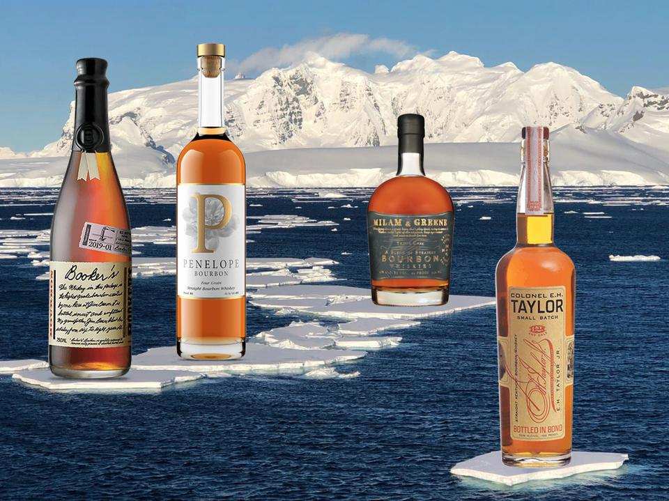 Four separate bottles of craft whiskey sit on icebergs floating in the sea.
