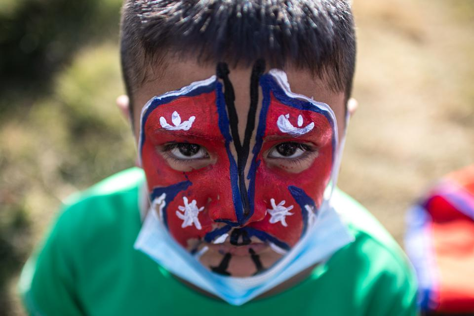 A Nepalese boy with the national flag painted on his face...