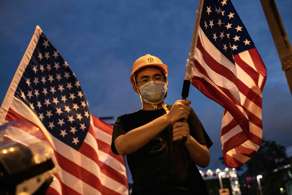 Demonstrator waves an American flag during the protest. Pro-...