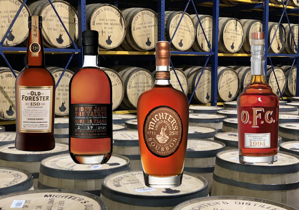 Four bottles of very expensive bourbon sit atop barrels in a Kentucky warehouse
