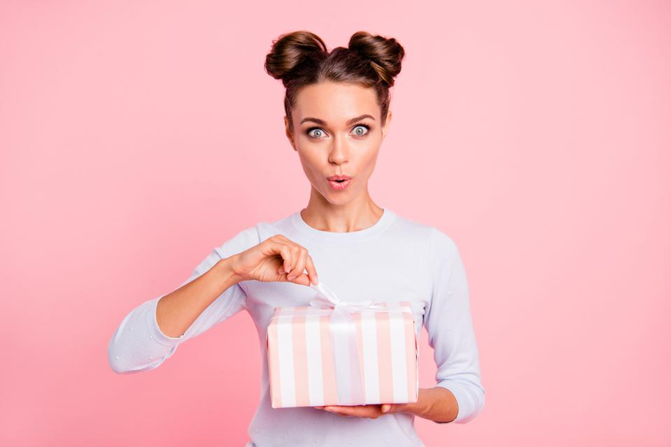 Beautiful woman opening a surprise gift.