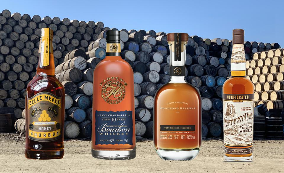 Four bottles of very expensive premium bourbon sit in front of a stack of barrels.