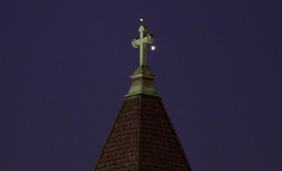 Saturn and Jupiter set behind a church ahead of their conjunction, as photographed on December 18, 2020 in Jersey City, New Jersey. (Photo by Gary Hershorn/Getty Images)