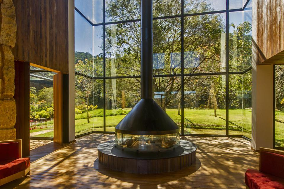 A large fireplace dominates the lobby of the Six Senses Botanique hotel in Brazil