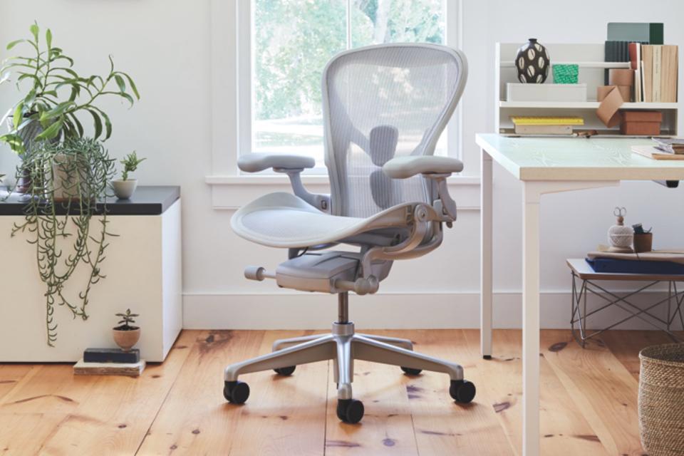Gray Herman Miller office chair set up on hardwood floor next to a desk.