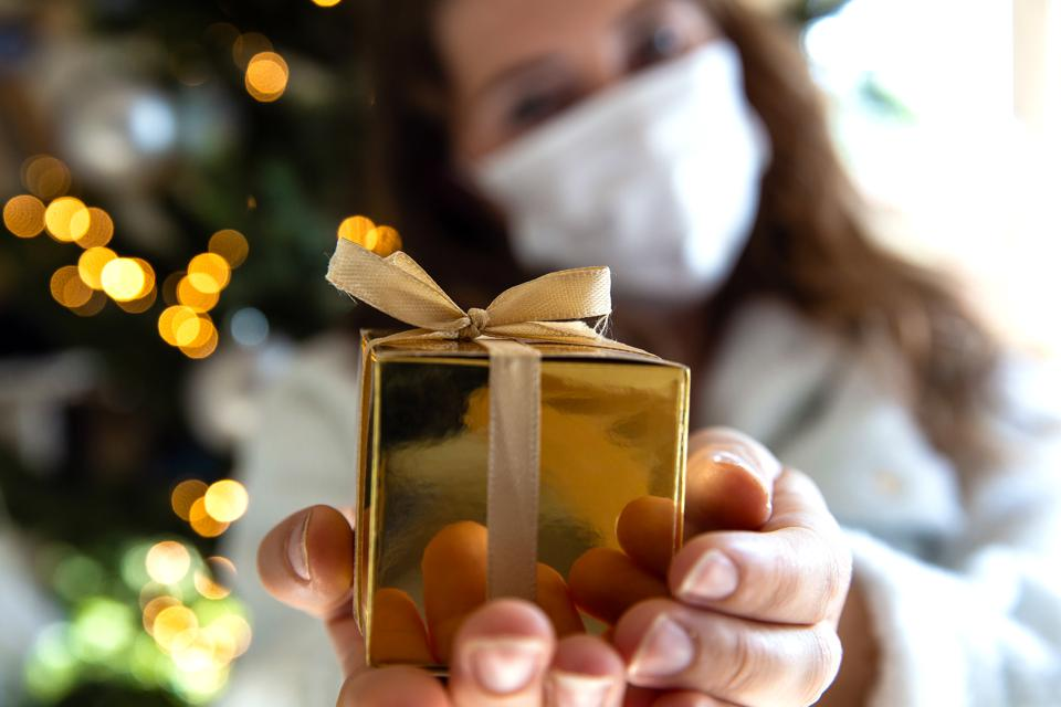 Young woman gives golden gift box wearing a protective Face maks for Covid-19, present and Coronavirus concept. social distance
