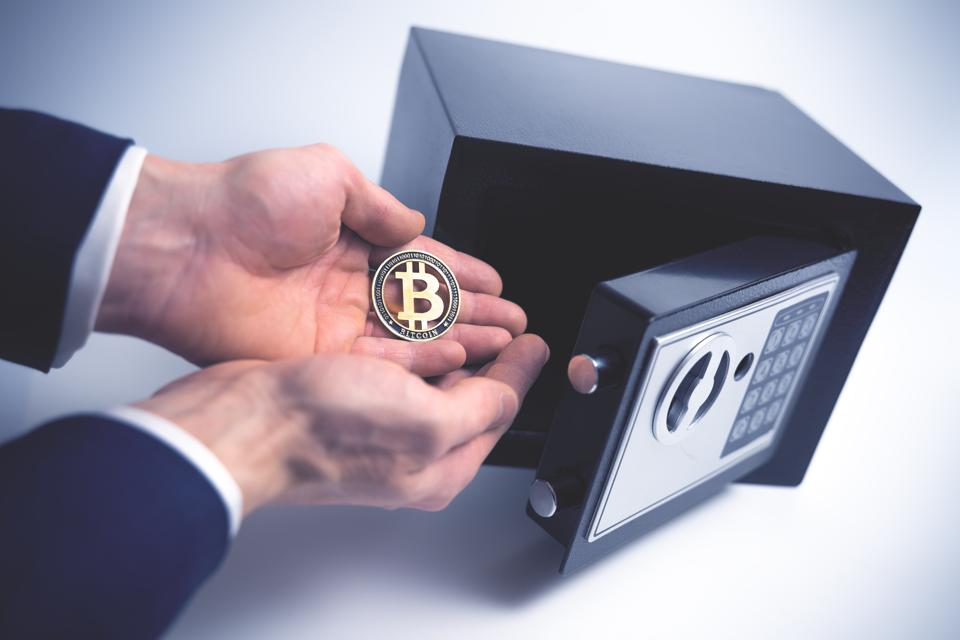 Safe Deposit. Symbol of cryptocurrency safety. The man puts a physical bitcoin in small Residential Vault. Toned soft focus picture