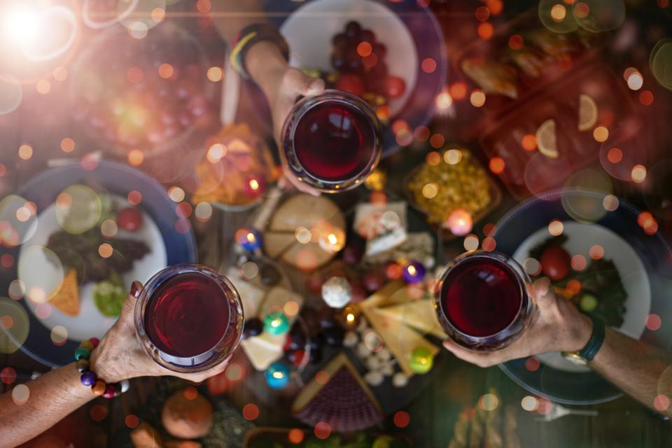Family Christmas dinner for a celebration with red wine and cheers.