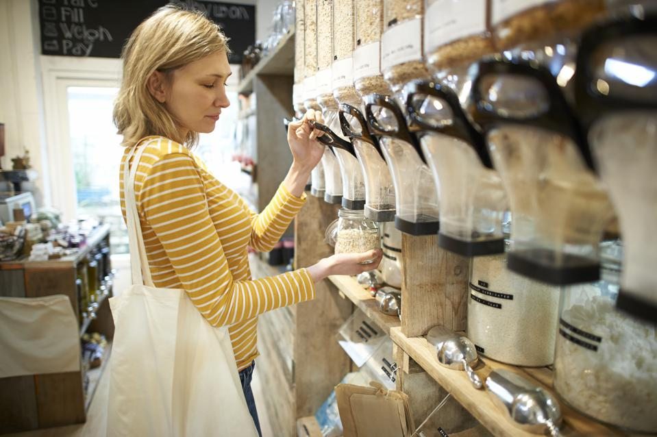 Woman in whole foods refill store dispensing oats into jar.