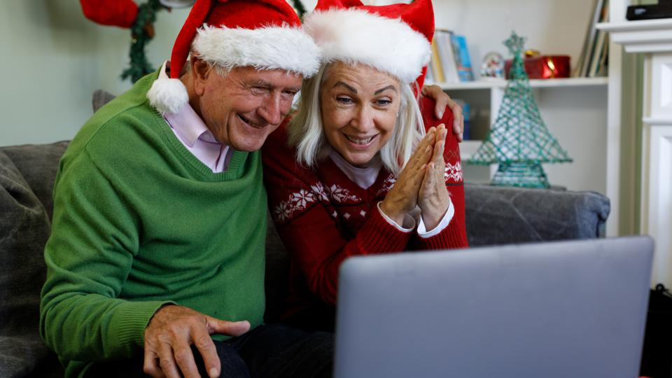 Senior couple in santa hat sitting on couch smiling while having a video call on laptop at home