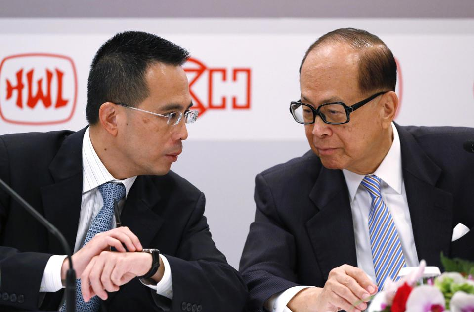 Victor Li speaks with his father, Li Ka-shing, during a press conference in Hong Kong.