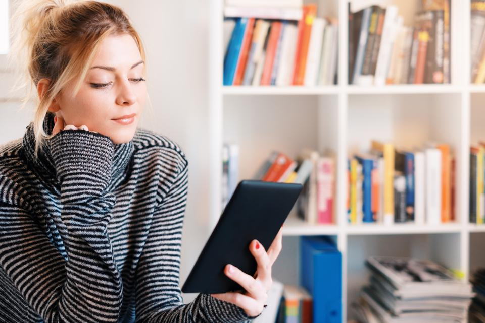 Young woman reading on e-book reader