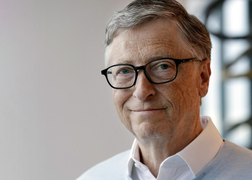 Bill Gates is white with gray hair, wearing black rimmed glasses and a blue sweater.
