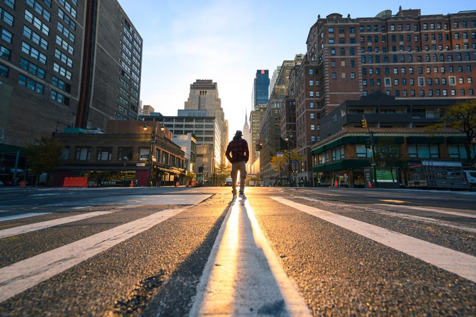 One person crossing a junction in Manhattan at sunrise, New York City