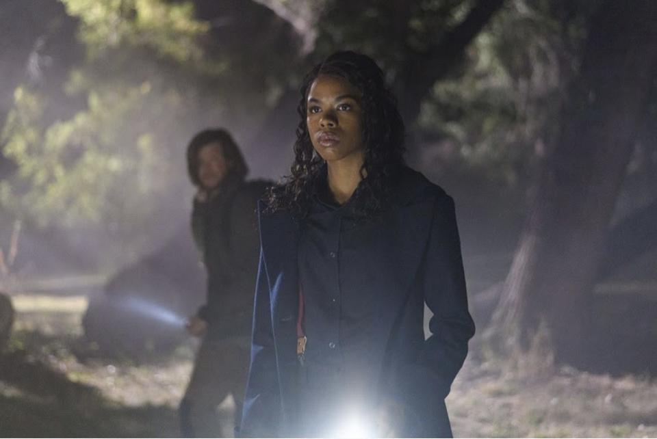 A Black woman in a navy blue coat stares with a man behind her.