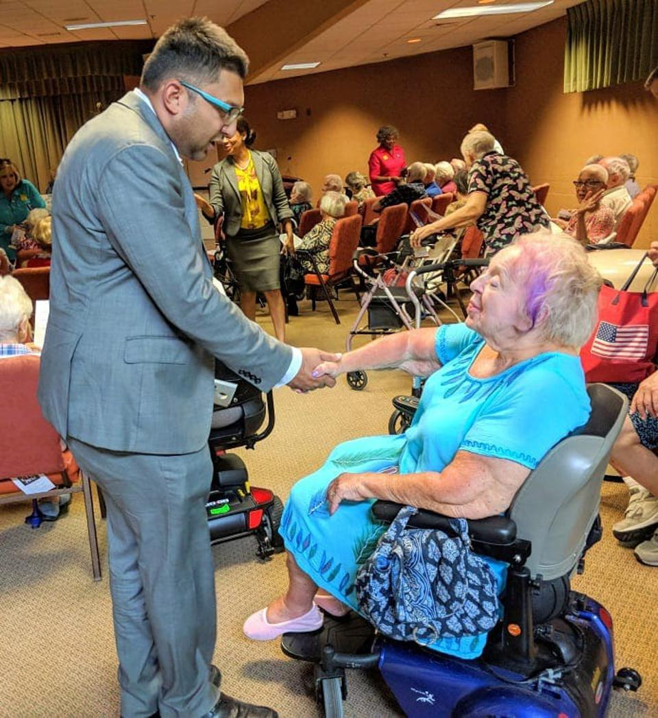 Man in a gray suit shaking hands with an older woman in a wheelchair.