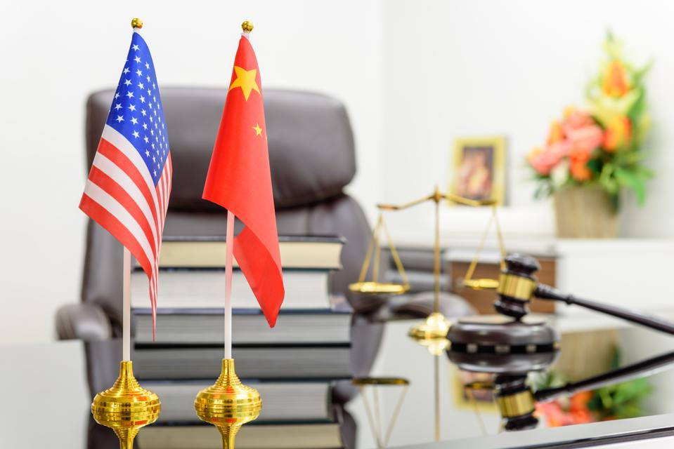 Flag of US USA and China put together on a table with books, gavel and a balance of justice behind. A symbol of cooperation between Washington & Beijing i.e. military dialogue, diplomatic negotiation.