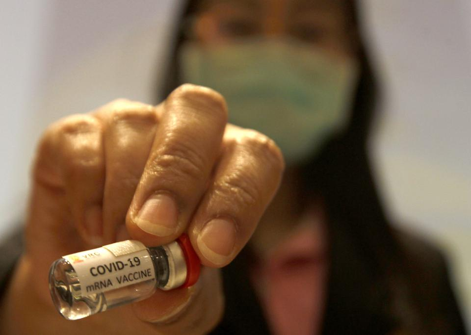 A researcher holds a COVID-19 mRNA vaccine during a news...