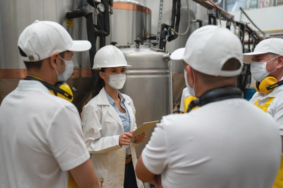 Engineer wearing a facemask while working at a brewery and talking to a group of operators in training