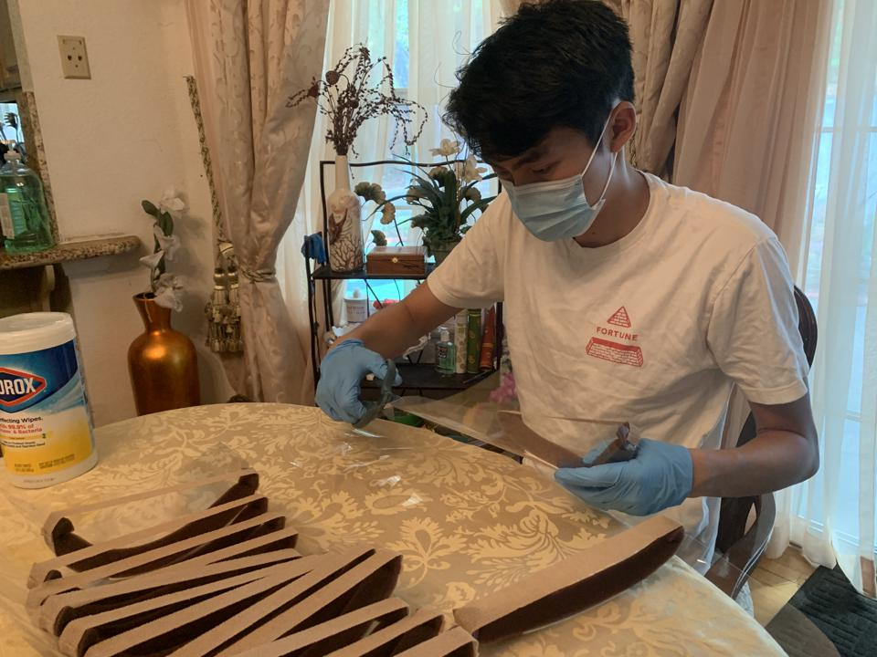 A young man in a face mask wearing gloves working with a sheet of plastic in kitchen