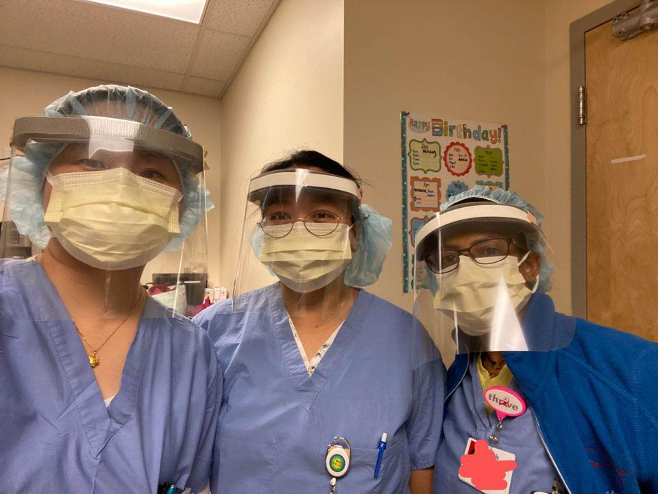 Three health care workers in blue scrubs and caps wear plastic face shields.