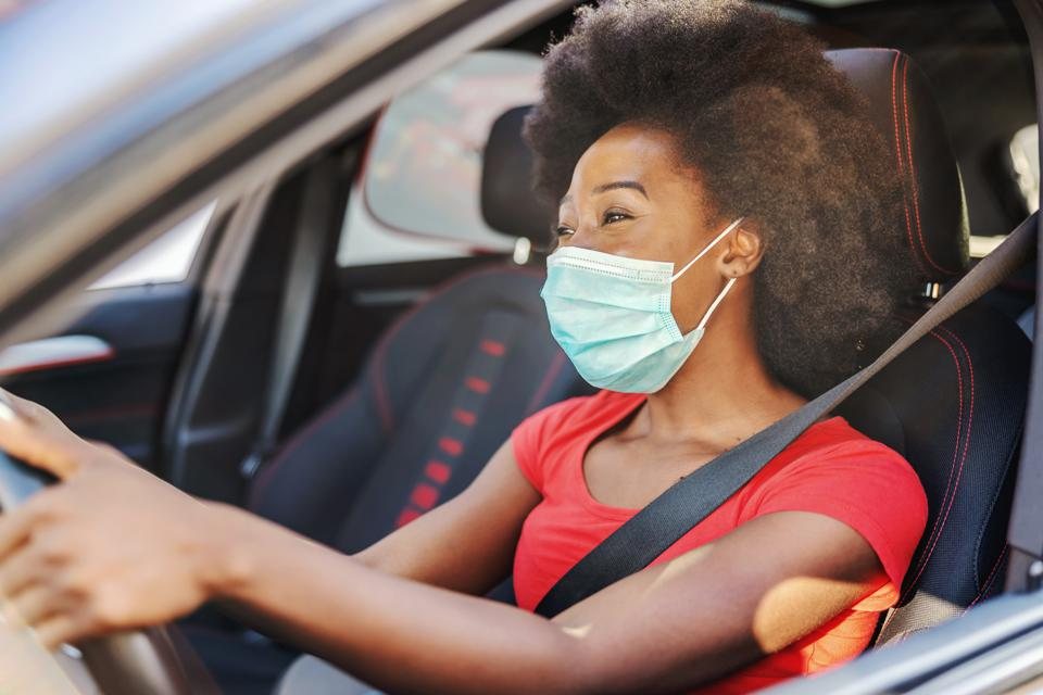 Young attractive african woman with mask on her face driving her car during covid-19 pandemic.