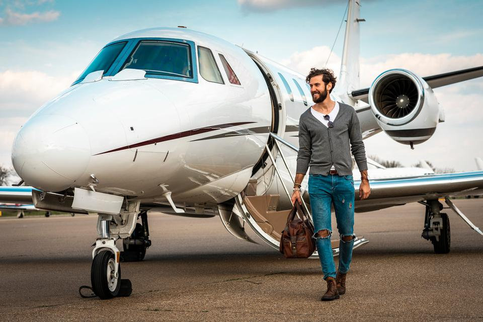 Successful man on jetway with private jet