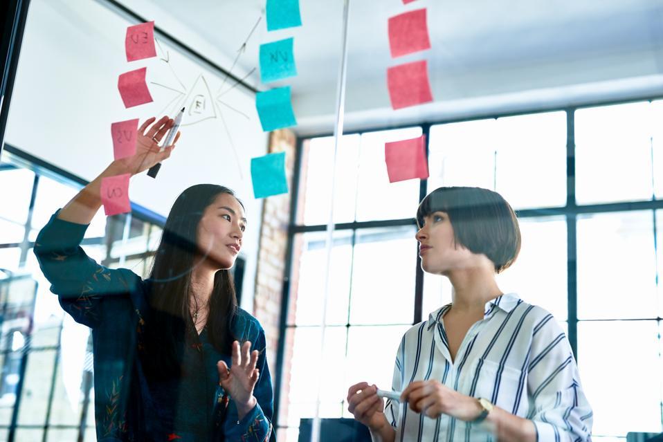 Businesswoman explaining diagram to female coworker
