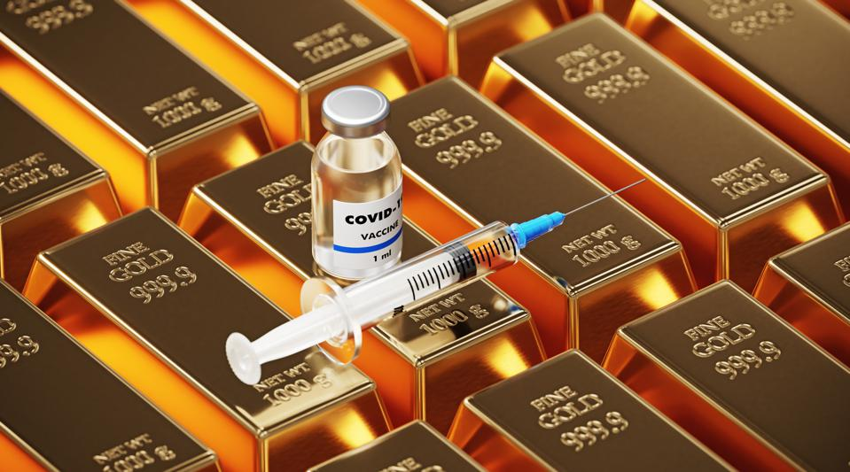 COVID-19 Vaccine Sitting Over Gold Bars Laying Next To Each Other