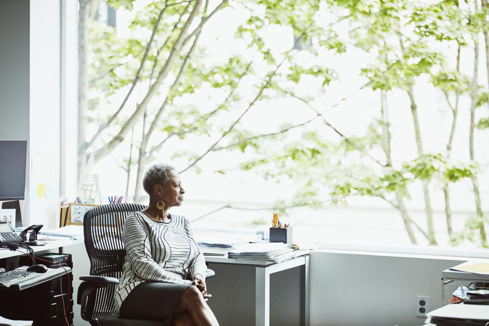 Businesswoman looking out window while sitting at office workstation