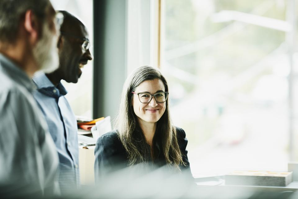 Portrait of smiling mature businesswoman in discussion with coworkers in office