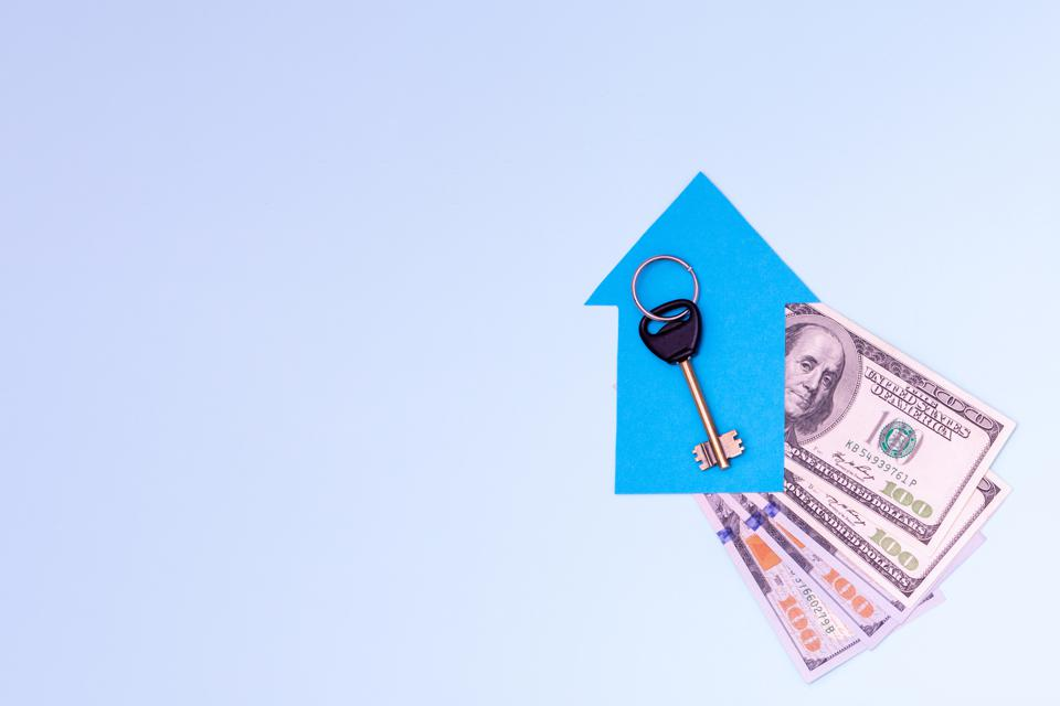 The key to a new apartment or house lies on a small blue paper house on a fan of 100 dollar bills