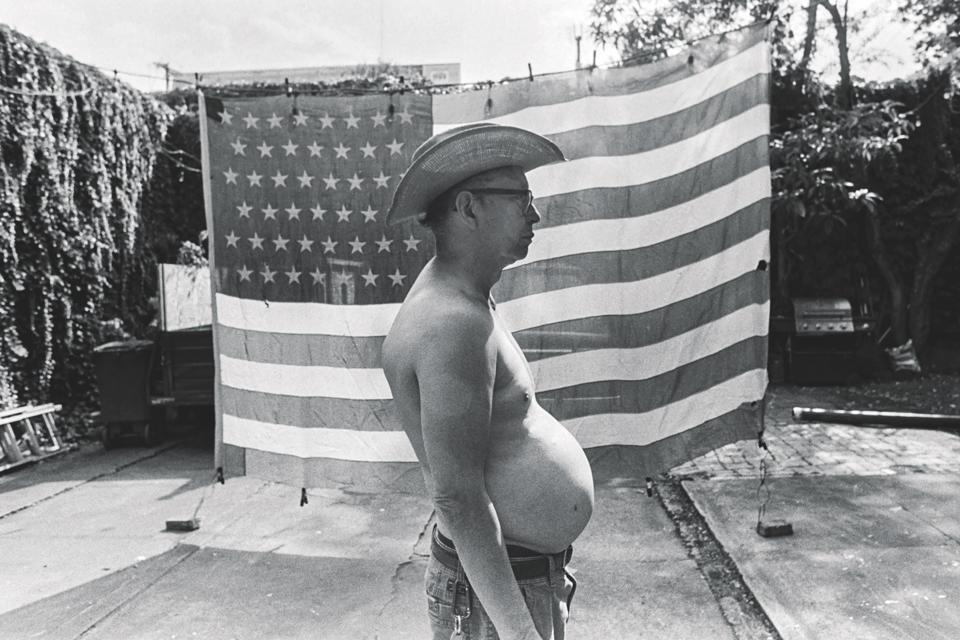A potbellied man stands in front of an american flag