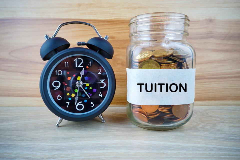 TUITION label with Golden coin inside jar and black alarm clock and wood background