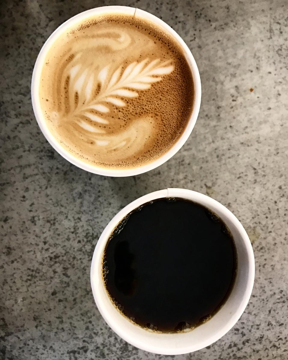 A Latte Sits Next to A Pour Over Coffee On The Counter