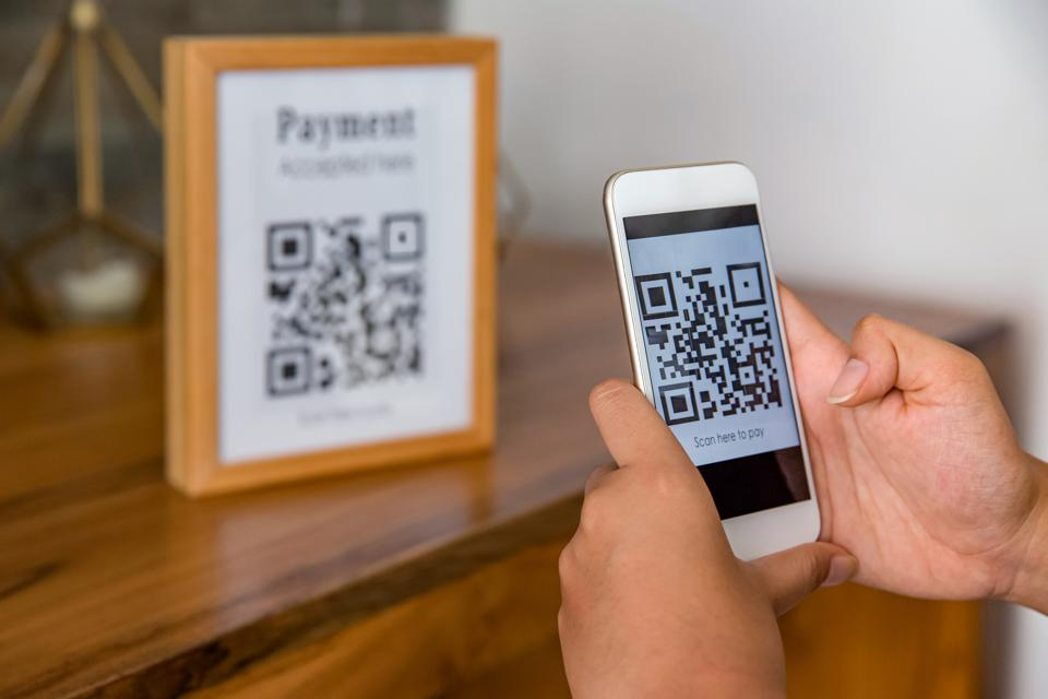 Asian Business woman using QR code mobile payment app