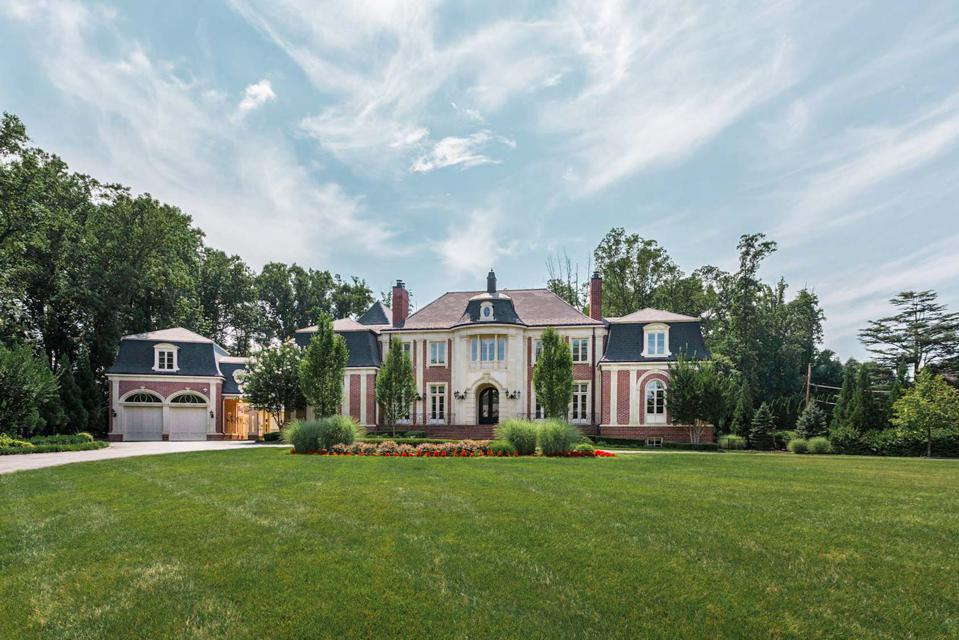 Stunning estate with grass lawn and blue and white sky.