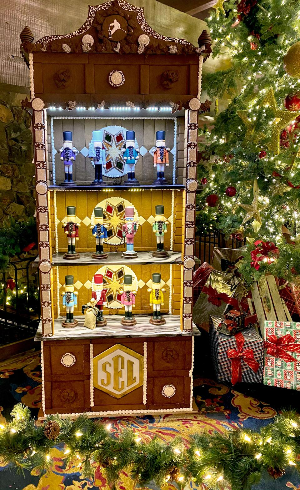 Antique gingerbread cabinet near Christmas tree.