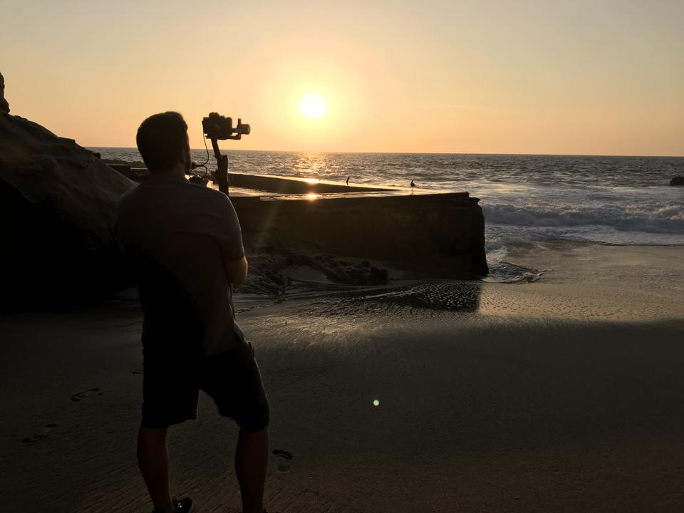 A camera operator stands with a camera on a sandy beach and films a sunset